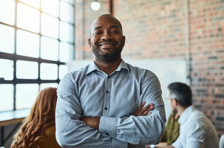 Happy man smiling at company practicing employee engagement