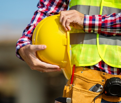 man holding hard hat and wearing safety vest being a safe employee on-site